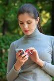 Kvinnan rymmer mobiltelefonen i hand Arkivfoto