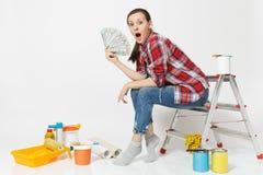 Kvinnan rymmer packen av dollar, kassapengar, sitter på stege med instrument för renoveringlägenheten som isoleras på vit royaltyfria foton