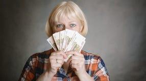 Kvinnan rymmer pengar royaltyfri bild