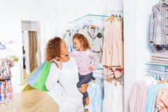 Kvinnan rymmer shoppingpåsar med hennes lilla dotter Arkivbilder