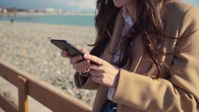 Kvinnan rymmer smartphonen i händer som står på havskajen i soligt väder arkivfilmer