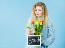 Kvinnan rymmer tulpan, bräde med text8 marsch Royaltyfria Bilder