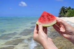 Kvinnan rymmer upp en skiva av vattenmelon på en strand i den Rarotonga kuttrandet Royaltyfri Bild