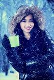 Kvinnan rymmer varmt te på vintern parkerar Arkivbild