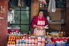 Kvinnan säljer gods på marknaden Royaltyfri Bild