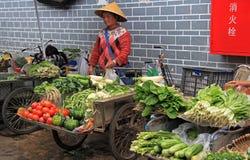 Kvinnan säljer grönsaker på marknaden in Arkivfoton