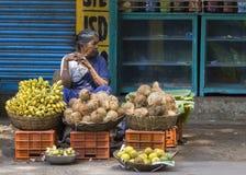 Kvinnan säljer kokosnötter och bananer Arkivbilder