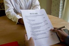 Kvinnan sänder platsansökan, intervjuaren som läser en meritförteckning arkivbild