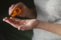 Kvinnan sätter en preventivpiller in i hennes hand från en preventivpillerflaska Arkivbilder