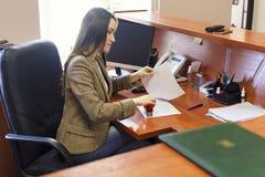 Kvinnan sätter en stämpel till dokumentet på skrivbordet Arbetet i kontoret royaltyfri bild