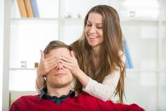 Kvinnan sätter hans hand över hans ögon en man för att göra honom en överraskning Arkivbild