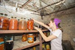 Kvinnan sätter krus med grönsaker och frukter i källaren med mat, för lagring på länge fotografering för bildbyråer