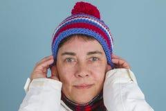 Kvinnan sätter på vinterlocket Arkivbild