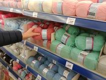 Kvinnan söker efter en boll av ull i en hylla av lagret Arkivbilder