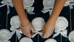 Kvinnan s- somhänder med vit manikyr på spikar, rätar ut en s-pilbåge-fnuren Det är vita godisar dekorerade paljettsötsaker lager videofilmer
