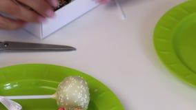 Kvinnan s?tter kakapop i en g?vaask Godisar dekoreras med en olik f?rgdressing och bandpilb?gar ?verskott sax f?r klippningar arkivfilmer