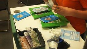 Kvinnan samlar kortet och pengar för identitet för medborgare för pass för anställningrekord i staden för barn` s arkivfilmer