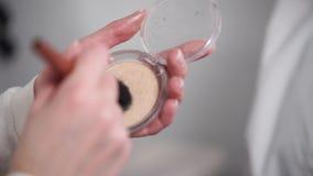 Kvinnan samlar pulver på en borste för sminket, närbild lager videofilmer