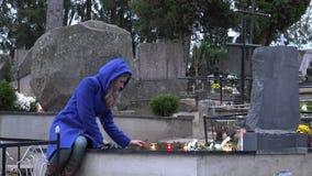 Kvinnan satte bränningstearinljuset på grav i kyrkogård i hösttid 4K lager videofilmer