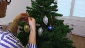 Kvinnan satte garneringar på julgranen arkivfilmer