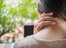 Kvinnan satte hennes hand på baksidan av hennes hals, medan känna sig smärta arkivfoton
