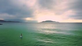 Kvinnan seglar på paddleboard mot rosa himmel bak ön lager videofilmer