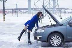 Kvinnan ser en bilmotor och innehav en manuell bil Arkivfoto
