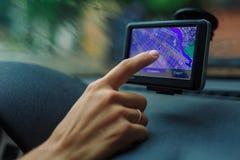Kvinnan ser en GPS navigatör i bilen Arkivbilder