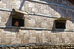 Kvinnan ser från fönstren av hennes hus, Bandarban, Bangladesh Arkivfoto