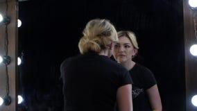 Kvinnan ser i spegeln och justerar hennes ögonbrynpincett stock video