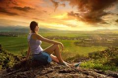 Kvinnan ser kanten av klippan på den soliga dalen av Royaltyfri Fotografi