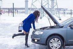 Kvinnan ser motorn av hennes bil och innehav en manuell bil Arkivfoto