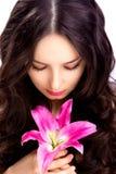 Kvinnan ser på blomman Royaltyfri Fotografi