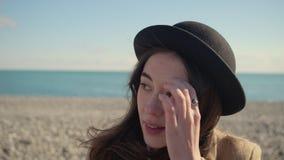 Kvinnan ser runt om att sitta i den soliga stranden som trycker på hår, närbildståenden arkivfilmer