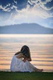 Kvinnan ser solnedgång över sjön Arkivfoton