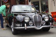 Kvinnan ser svarta Jaguar 3 typ för s 8-litre (1965) Arkivfoton