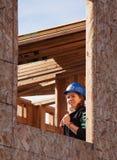 Kvinnan ser ut det oavslutade fönstret av hemmet för livsmiljön för Humani Arkivfoton
