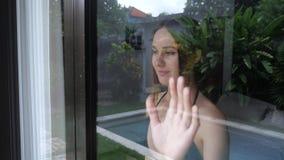 Kvinnan ser ut fönstret och säger farväl till någon och att vinka hennes hand 4k ultrarapid lager videofilmer