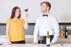 Kvinnan ser vinet i exponeringsglas royaltyfri foto