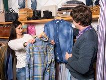 Kvinnan shoppar assistentvisningskjortan för att man Arkivfoto