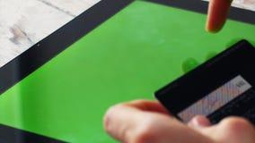 Kvinnan shoppar direktanslutet med minnestavlaPC:n, tom grön skärm arkivfilmer