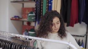 Kvinnan shoppar i klädlager i gallerian som tar hängare från kuggen arkivfilmer