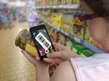 Kvinnan shoppar i supermarket och avläsande barcode med smartphonen i livsmedelsbutik royaltyfri bild