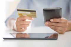 Kvinnan shoppar på internet med smartphonen och kreditkorten Royaltyfri Foto