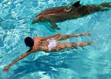 Kvinnan simmar i havet nära en delfin royaltyfri bild