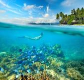 Kvinnan simmar runt om en härlig korallrev Arkivfoto