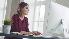 Kvinnan sitter framme av datorbildskärmen och skrivar ut en text, ler arkivfilmer