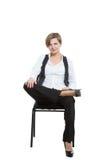 Kvinnan sitter grensle en stol korsade ben, fixat Fotografering för Bildbyråer