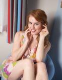 Kvinnan sitter, i att le för stol fotografering för bildbyråer