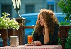 Kvinnan sitter i kafé Royaltyfri Bild